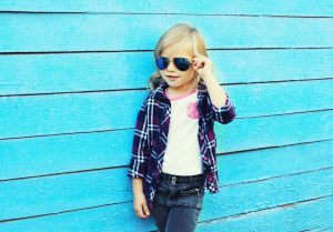 Fashion kid, stylish child wearing a sunglasses and checkered shirt standing over blue background, looking away